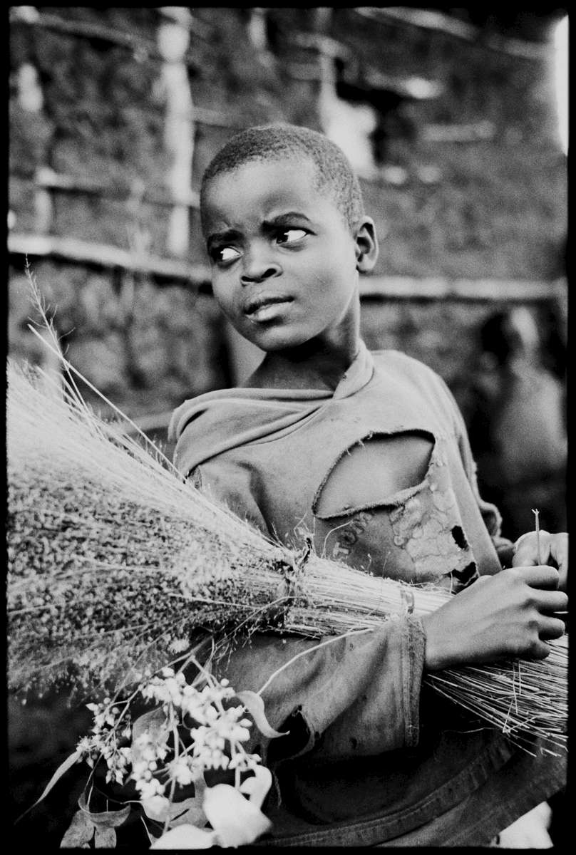 A young boy holds flowers outside his family's home in rural Butare, Rwanda.