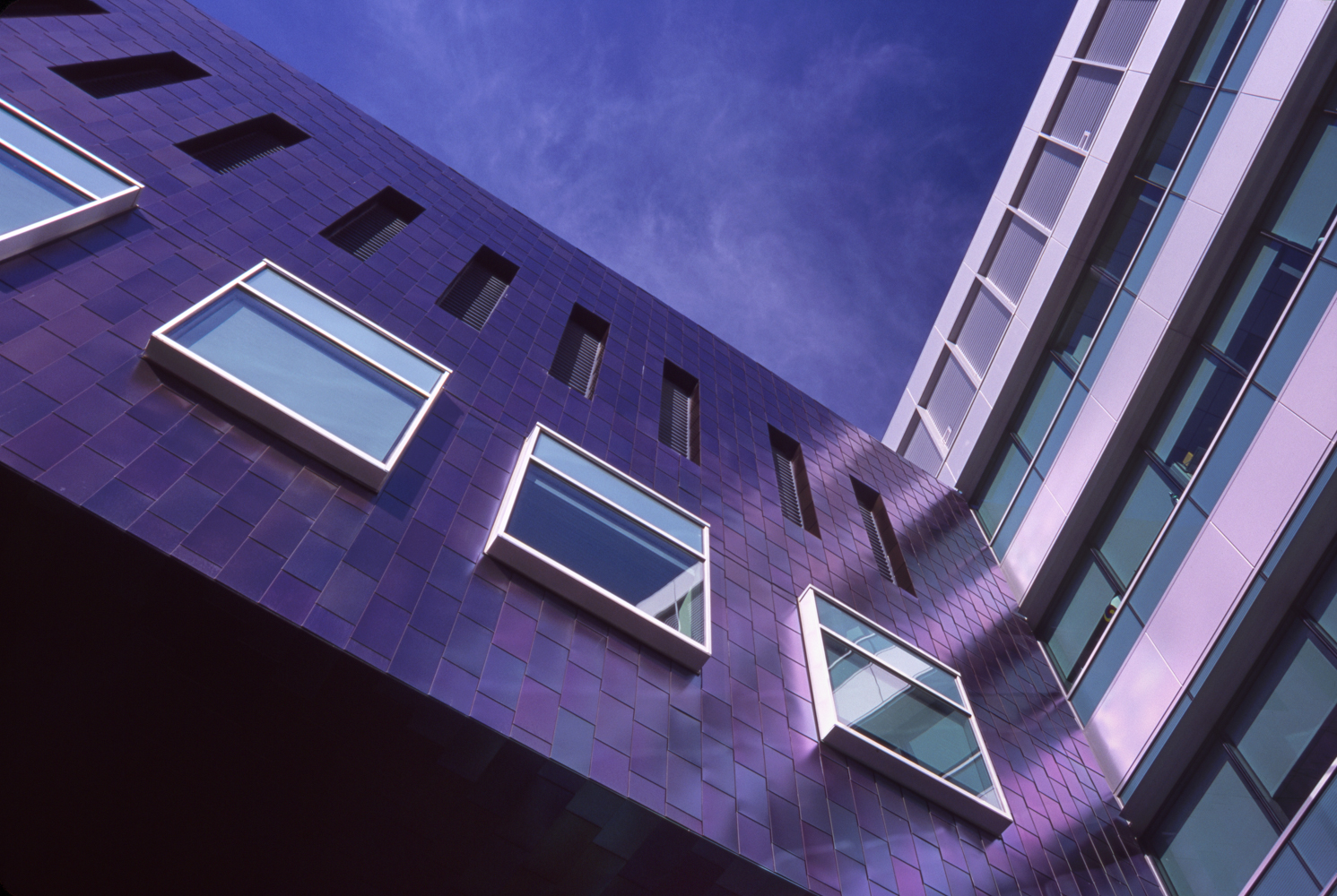 Zimmer Gunsul Frasca Architects selected stainless steel shingles for parts of the exterior of Moores Cancer Center, UC San Diego, in La jolla, California.  The panels are acid-etched, have an iridescent appearance, and depending on the sky light can appear green, blue, or purple.