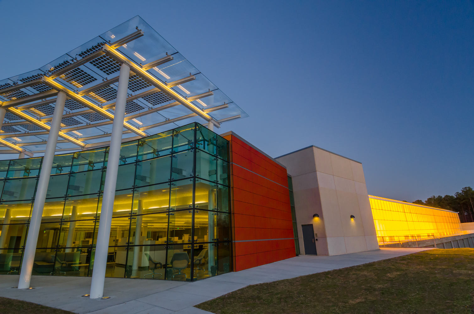 Solar panels on the glass portico of this crop science facility help power the enclosed research and greenhouse spaces.