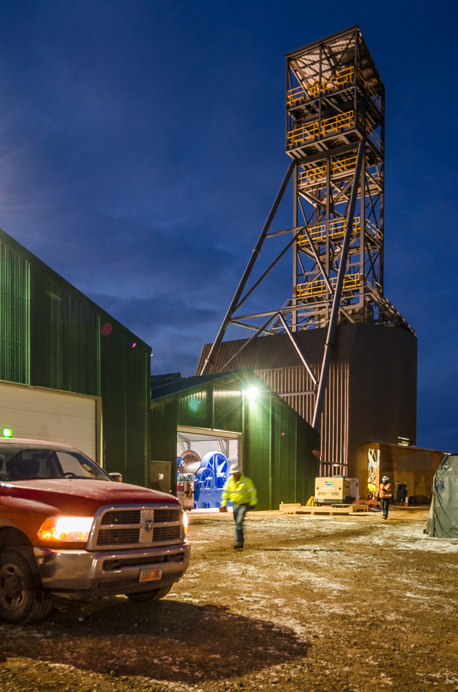 An engineer and a safety officer cross the work yard of a gold mine in Nevada, passing the elevator engine house and the mine shaft tower.