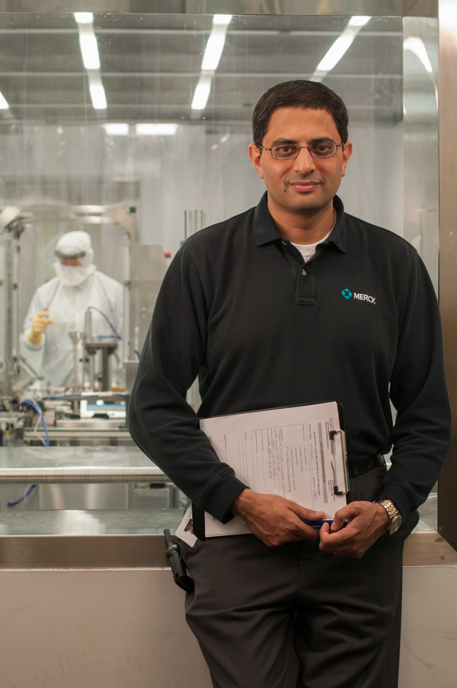 An RTP pharmaceutical specialist pauses at the observation window of a vaccine manufacturing facility clean room.