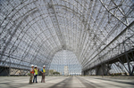 Hangar One, completed in 1933 to house  the naval airship USS Macon, covers eight acres.  The exterior panels were removed in 2011-2012 due to leaking toxic chemicals and asbestos.