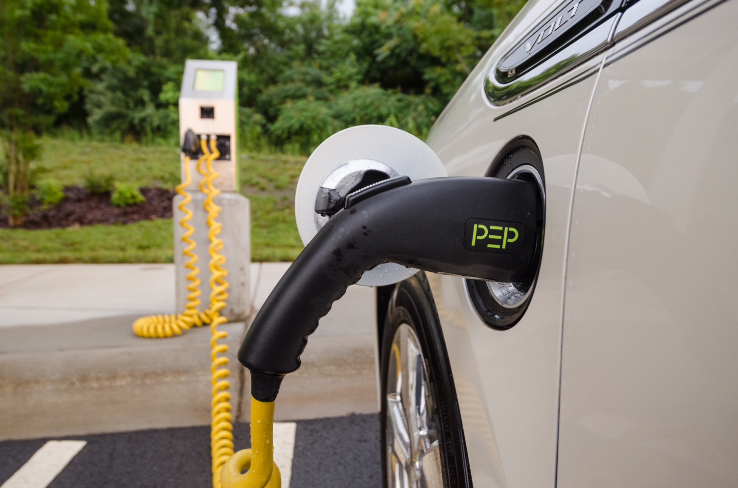 This hybrid Chevy Volt is being charged at a pep charging station that takes advantage of solar panels on the canopy overhead.