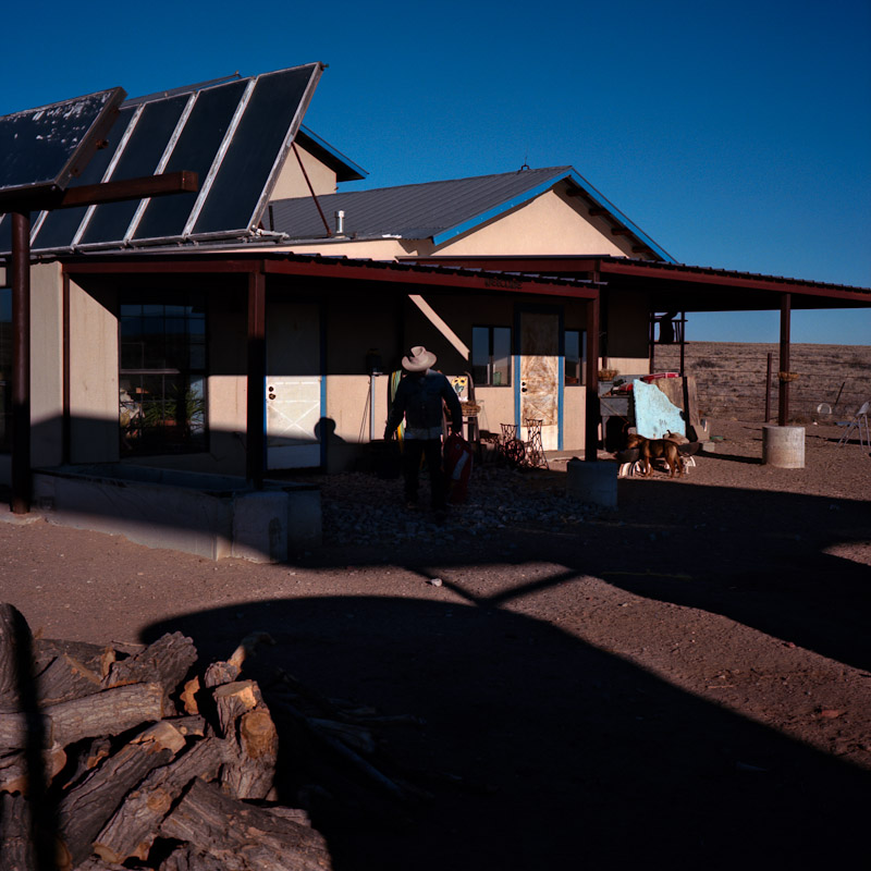 Carlos Proffit outside of his home in Pajarito Mesa. Mr. Proffit moved to the Mesa {quote}to escape the rent cycle,{quote} and then built his own home. He slowly learned to install and in some cases build solar and wind solutions for his home over the course of many years.