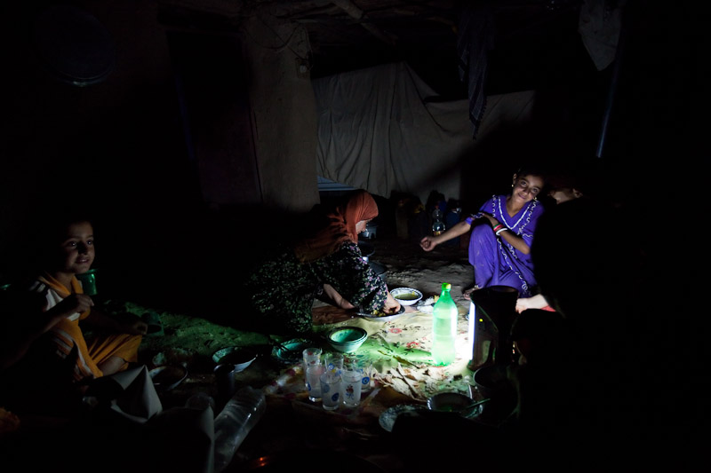 A family eats dinner by flashlight in their home in Binika, Kifree District, Kurdistan, Iraq. Binika was once a thriving community with over 150 families, electricity, schools, and a clinic, but it was never completely rebuilt after Saddam Hussein's 1988 genocide against the Kurds.