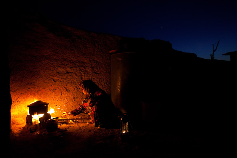 Kharaman Ibrahim Mohammed feeds a small cooking fire as she prepares dinner for her family in Showara.