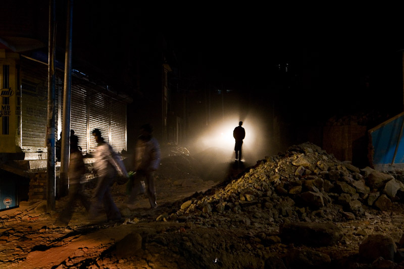A street in Kathmandu, Nepal lit only by the headlights of a car. Across Nepal, from rural villages to Kathmandu, most people are forced to live and work without light, despite the fact that Nepal is a nation with huge hydropower potential.