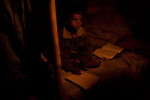 A young boy studies by candlelight at night in Kathmandu.