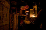 A woman enters her shop, lit only by candlelight, in Kathmandu.
