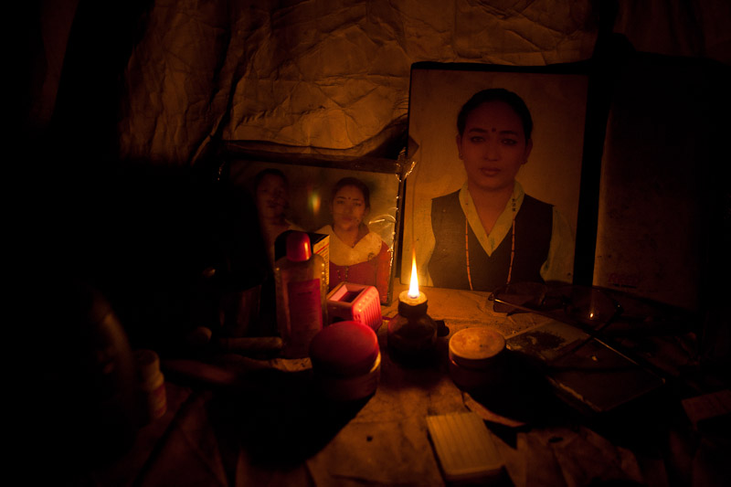 Family photographs are lit by the light of a small oil lamp in Kathmandu.