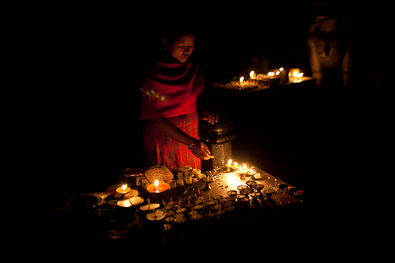 A woman lights a candle outside a temple in Kathmandu.