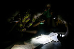 Children read the Koran by flashlight at a mosque in Wantugu.