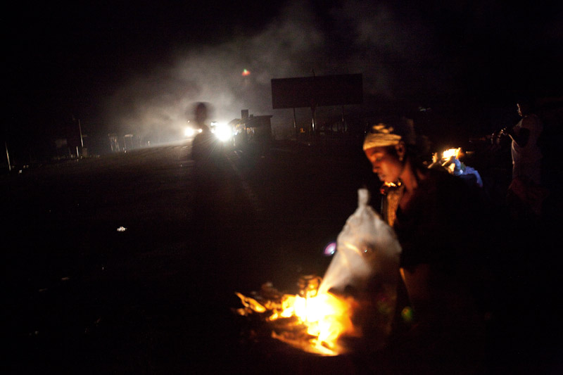 A woman sells food by the roadside in Fulfusu Junction, Ghana. The town is located at a major junction on northern Ghana's main road, between several large cities and the north's most popular tourist destination. Residents argue that electricity would allow them to capitalize on the tourism and service industries and cater to passing truck drivers crossing from north to south.