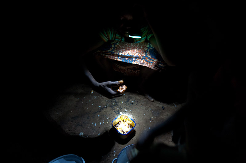 A young girl eats dinner in her home in Voggu.