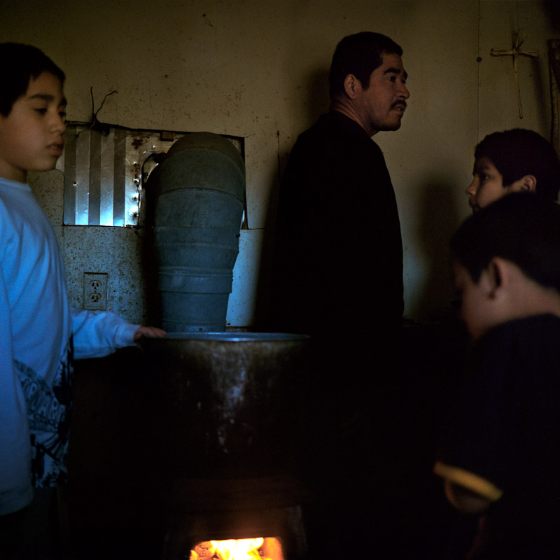 Members of the Alcudia family crowd around a wood stove for warmth in the early morning.