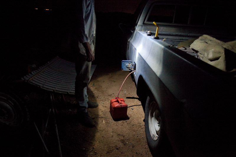 A man siphons gasoline out of his truck so that he can use it to power a generator for a couple of hours in his trailer.