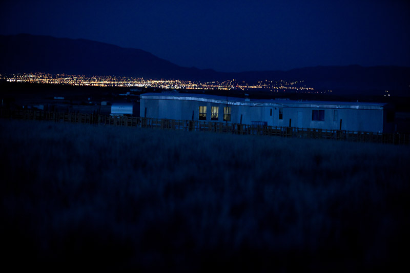 The lights of nearby Albuquerque shine in the distance behind a trailer in Pajarito Mesa, New Mexico.