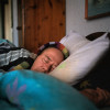 Richard asleep with all of his clothes on and a scarf to keep him warm in his home in Solihull.