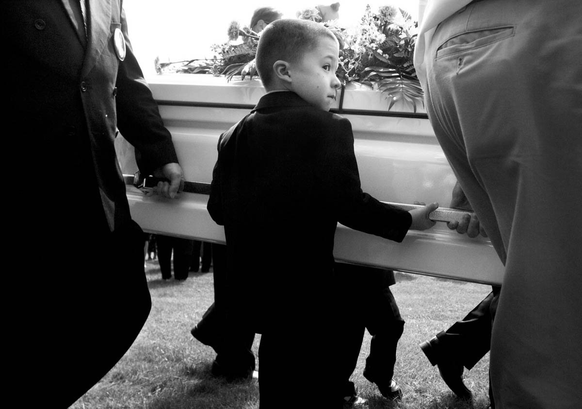 Seven-year-old Mac and six-year-old Ryan, on the other side of the casket, step in as pallbearers, helping to carry their sister from the hearse to the cemetery.