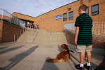 Brendan waits with Buster outside of Washington Middle School on the first day of school.  It was the first day of school for both of them.