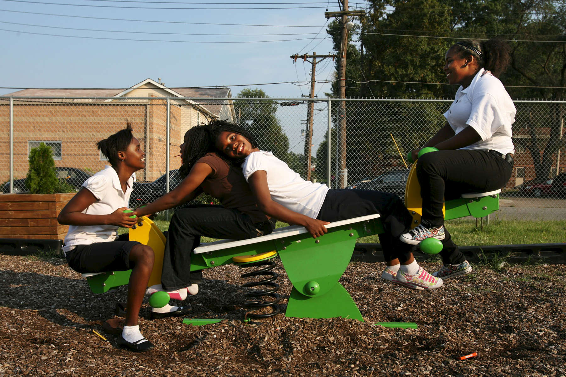 Twelve-year-olds Lacey McCray, Amahjanee' Patterson, Airriona McCray, and Tamijah Murphy crowd onto the teeter-totter on the playground across the street from the Christian Activities Center in the Olivette Park neighborhood in East St. Louis. A bar used to occupy the land where the playground sits. In 2005 the CAC purchased it with the hopes of adding the playground and the eventually a fine arts center and a dormitory for volunteers.