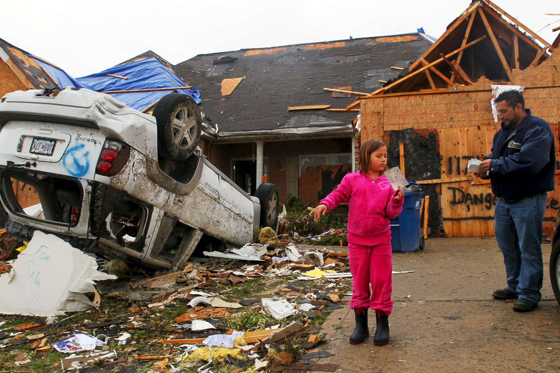 Sophia Zegar, 8, asks her father Sergio if the photo she found in their yard was theirs. It wasn't. Sophia, Sergio and his sister were home when the storm hit. After hearing the sirens and warnings on TV they took refuge in the bathroom in their basement. {quote}I think God's hand was protecting it,{quote} Sergio said of the room.