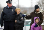 Left, Kirkwood police officer Dave Docter, Kirkwood police court clerk Kathy Hatcher, Kirkwood residents Kimberly Garritson and her daughter Anna Wells, 6, watch as Kirkwood Police Officer Thomas Ballman's funeral procession passed the Kirkwood police station.