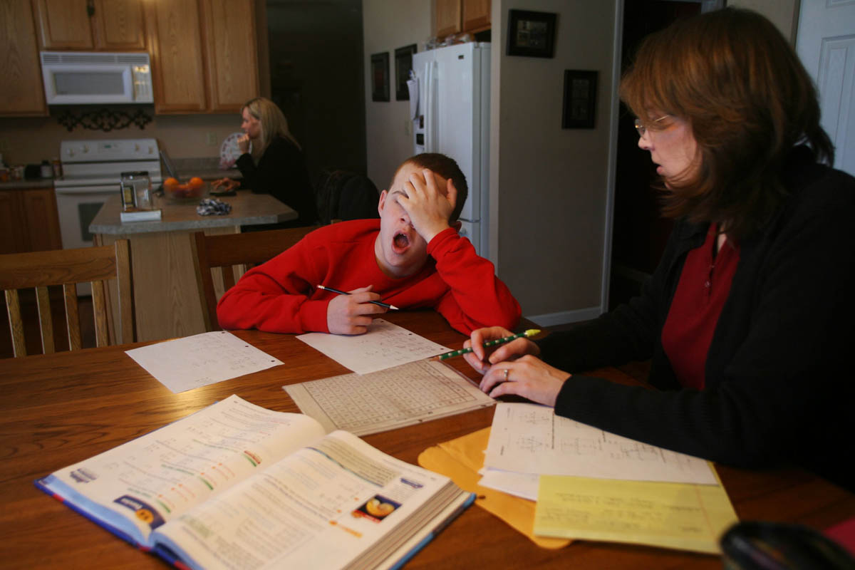 Homebound teacher Claire Kujath helps Brendan with his math homework over Christmas break. Because Brendan misses so much school with his medical appointments and treatments he has teachers come to his house to help him keep up.