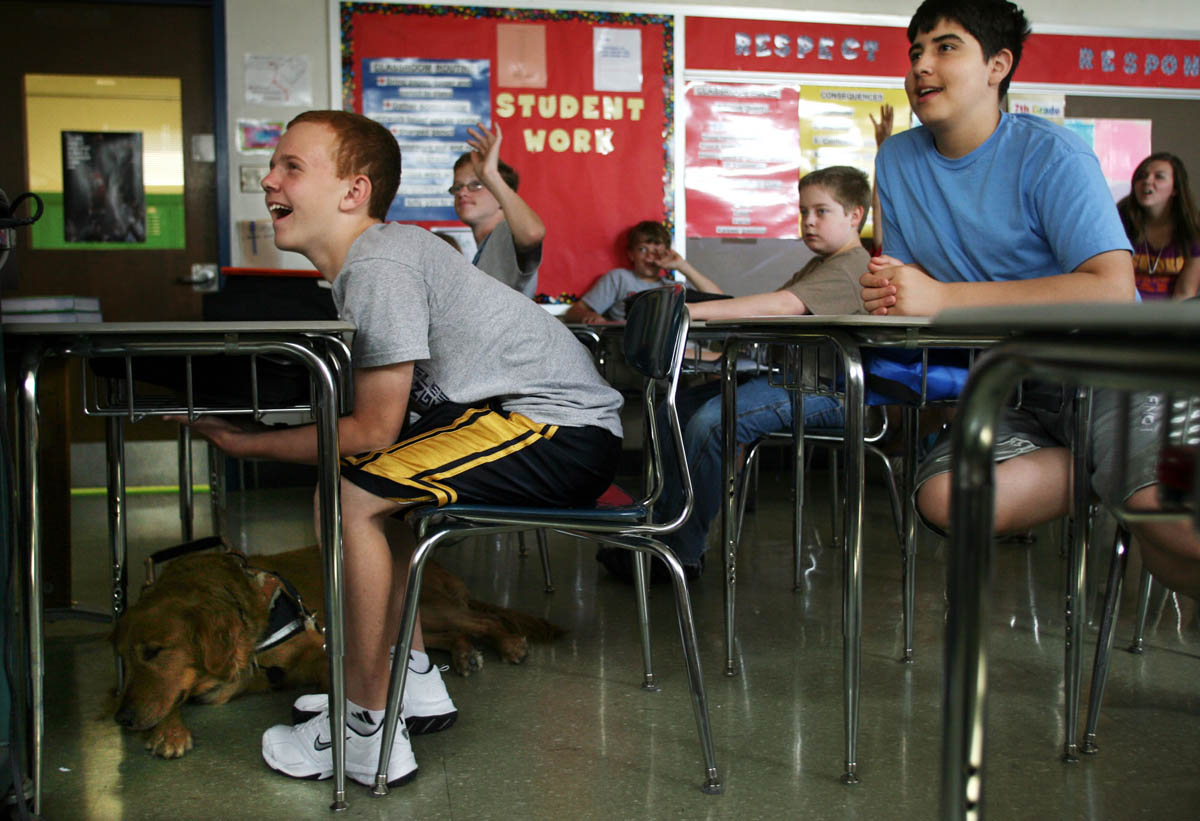 Brendan sits in Scott Simmons' Literature class at Washington Middle School during his last week of seventh grade. Brendan's seeing eye dog Buster lays under his desk. Buster spent the year helping out Brendan, whose eye sight comes and goes.