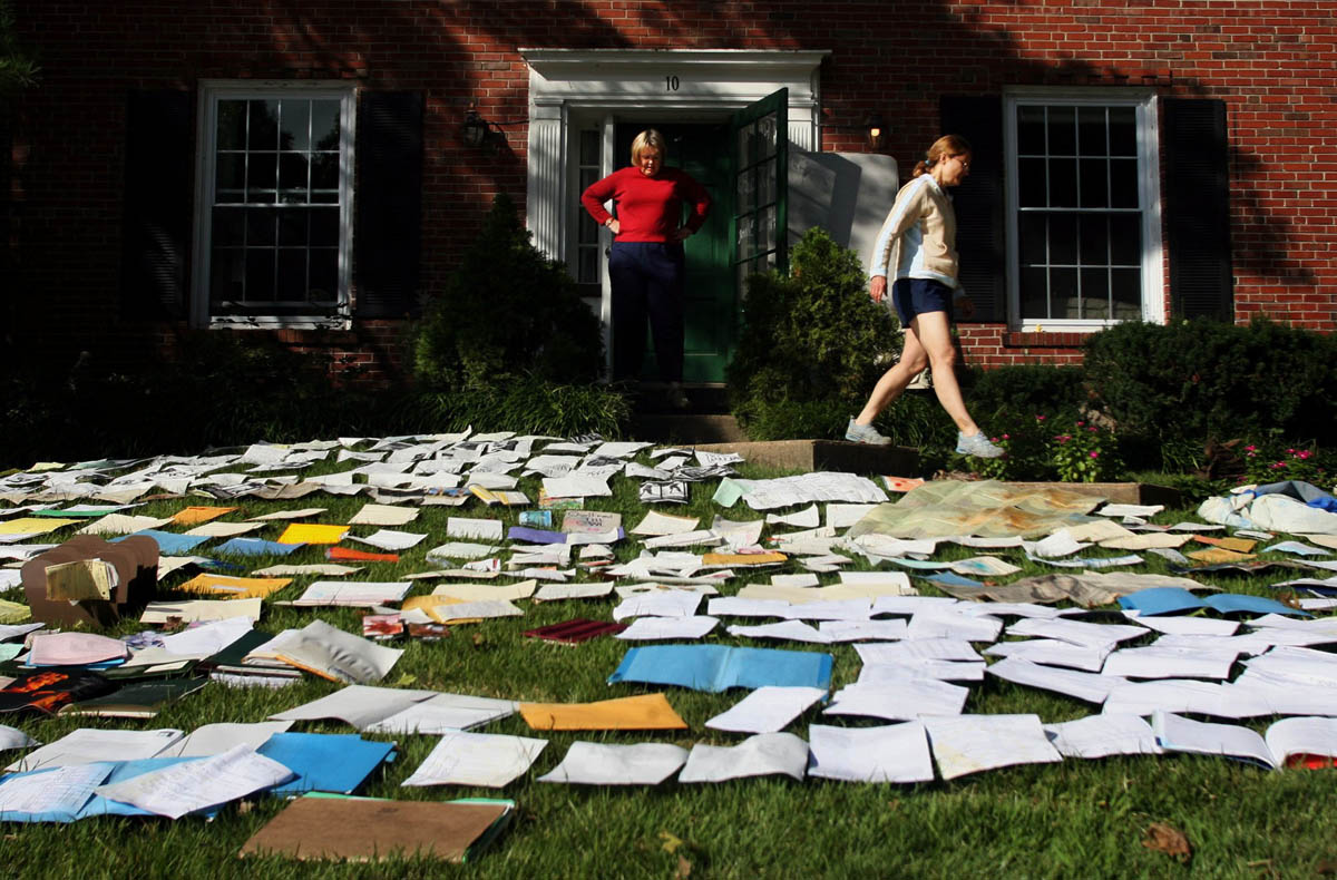 Yvonne Pierce walks out of her house as Kathryn Pierce stands and looks at the hundreds of documents spread across the lawn at Yvonne's home on Haddington Court in Clayton. The front lawn was covered in hundreds of wet family documents that were recovered from the flooded basement and layed out to dry.  Pierce said their street flooded Sunday morning when the sewer backed up during the storm.