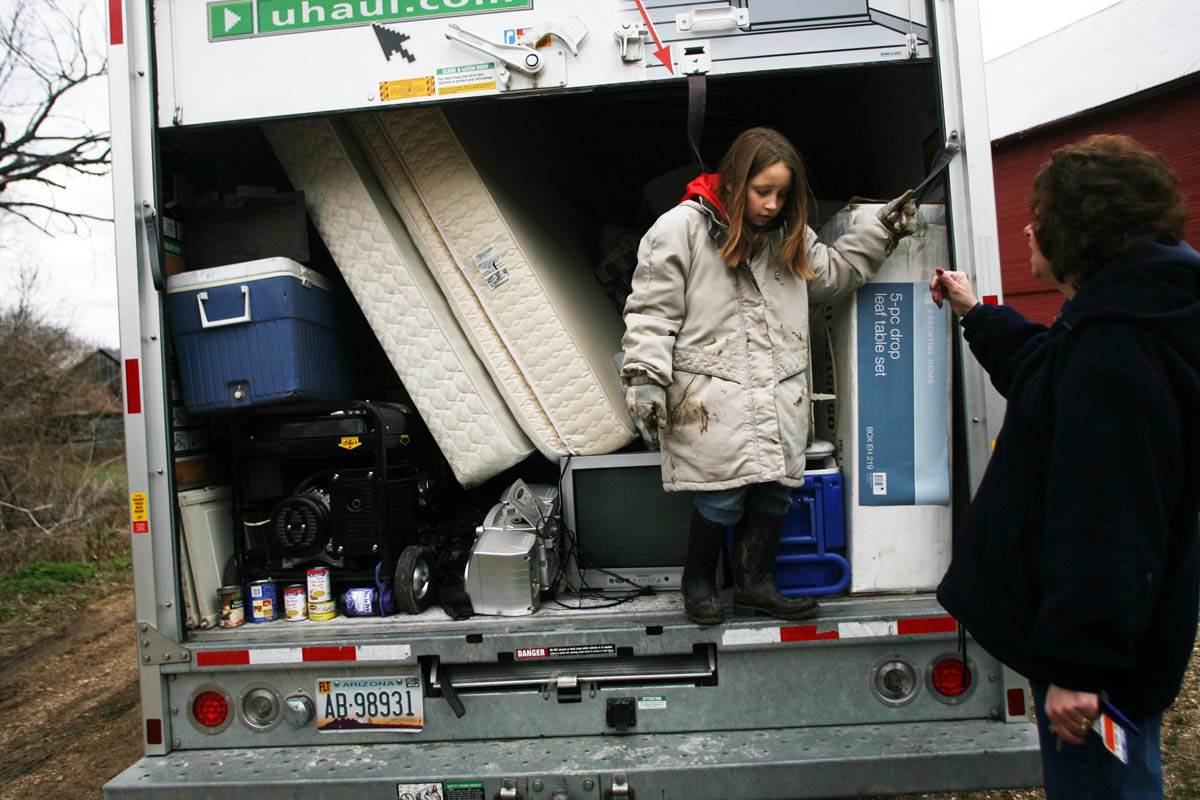 Natalie Lamkemeyer, 9, stands on the Uhaul truck next to her mom Kathy Sunday as they look through things they want to take with them after they were forced out of their home by the flooding of the Big River in Jeffereson county.  The family got the truck to move their possesions from the first floor of their home and parked it at a friends house on higher ground to keep it safe.