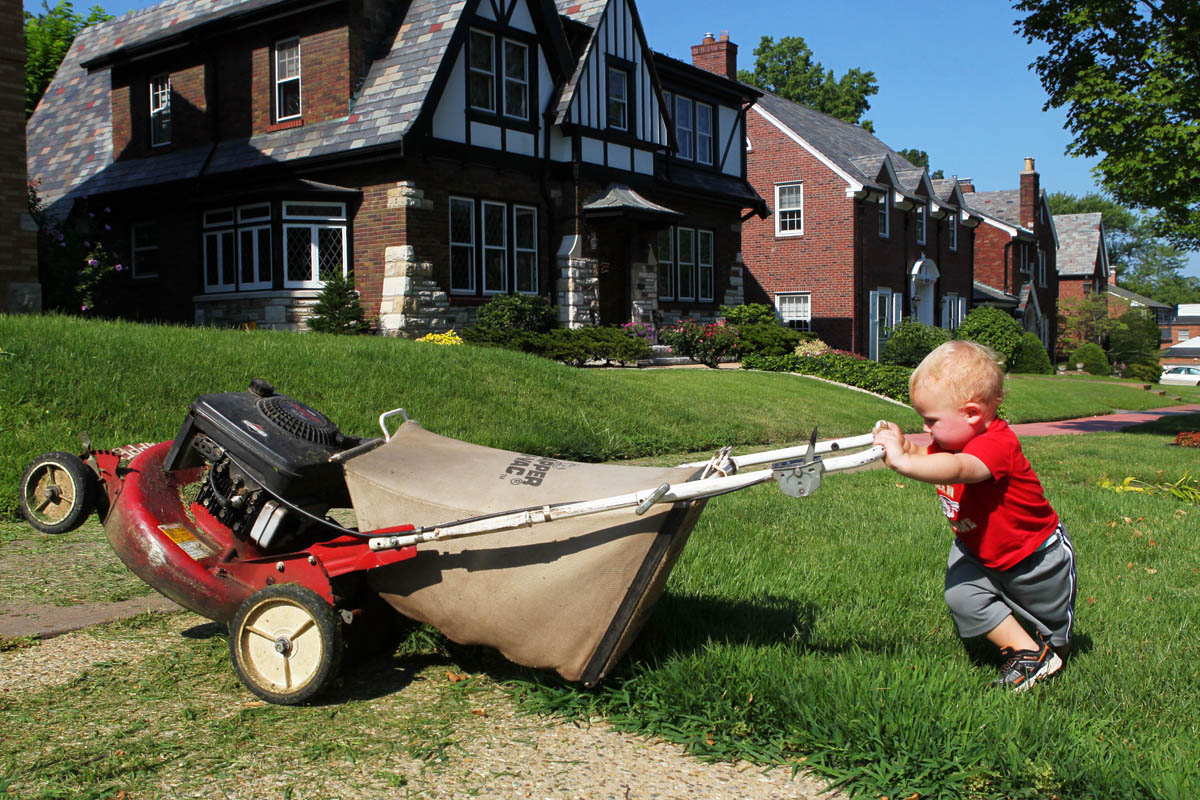 Fifteen-month-old Lucas Grosswiler helps out his dad with yard work Monday morning at their home in St. Louis. Lucas' father Tim (not pictured) was nearby trimming the lawn.