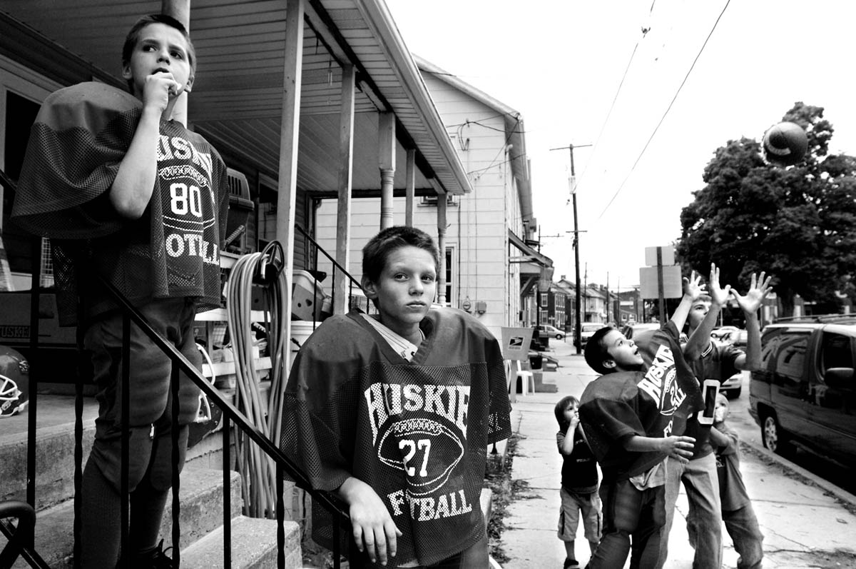 For three young boys the start of football season cannot come too soon.  Brandon Petrick, 12, looks out from the top step of their porch, his cousin Matt Myers, 12, stands a few steps down, while Petrick's brother Bradley Hopkins, 9, stands on the sidewalk and tosses a ball with a neighborhood friend.  The older boys' eyes dart from one direction to the other as they watch each passing car hoping to spot their ride to the first scrimmage of the year.  For two of the boys, this is their first year playing for the Hanover Huskies.
