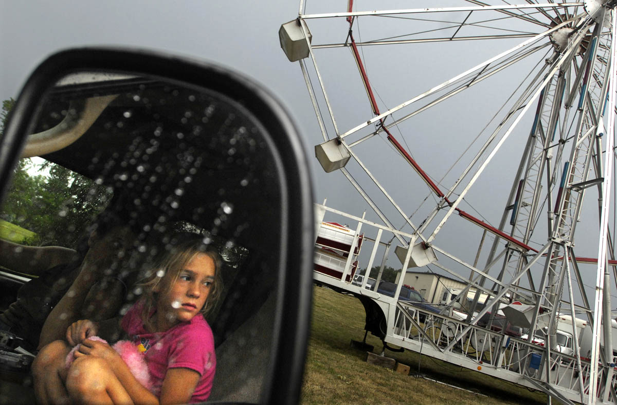 Mikayla Long waits inside her mother Tammy's truck at the Bonneauville Fire Carnival on her 8th birthday.  Long, along with her mother and brother  were waiting for the rain to stop so they could set up the climbing wall.