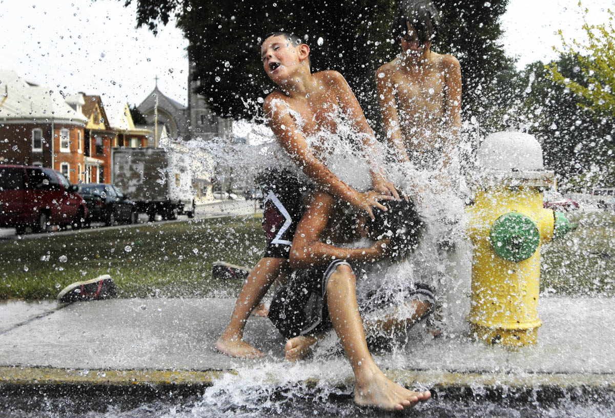 Brent Petrick, 15, Cody Racine, 8, Brandon Petrick, 12, and Bradley Hopkins, 10 pile onto each other at the open fire hydrant near Wirt Park in Hanover. The three brothers and their cousin found the fire hydrant while delivering newspapers and decided to cool down in the gushing water on their way home.