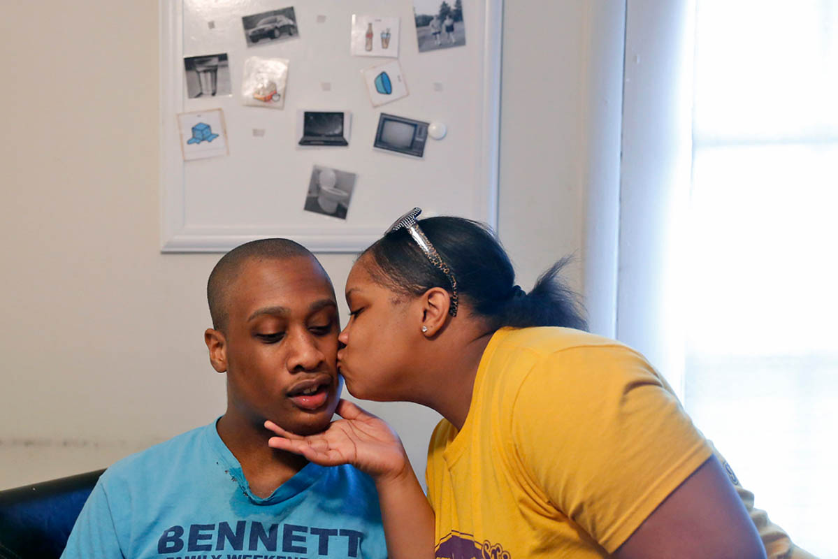 Tonnette Bennett stands kisses 18-year-old Patrick Lucas, Wednesday afternoon. Lucas has Fragile X Syndrome, which causes him to function at 3-year-old level. He was enrolled in a special-needs after school program before it was suspended in December. The city of Newport News is planning to eliminate the program.
