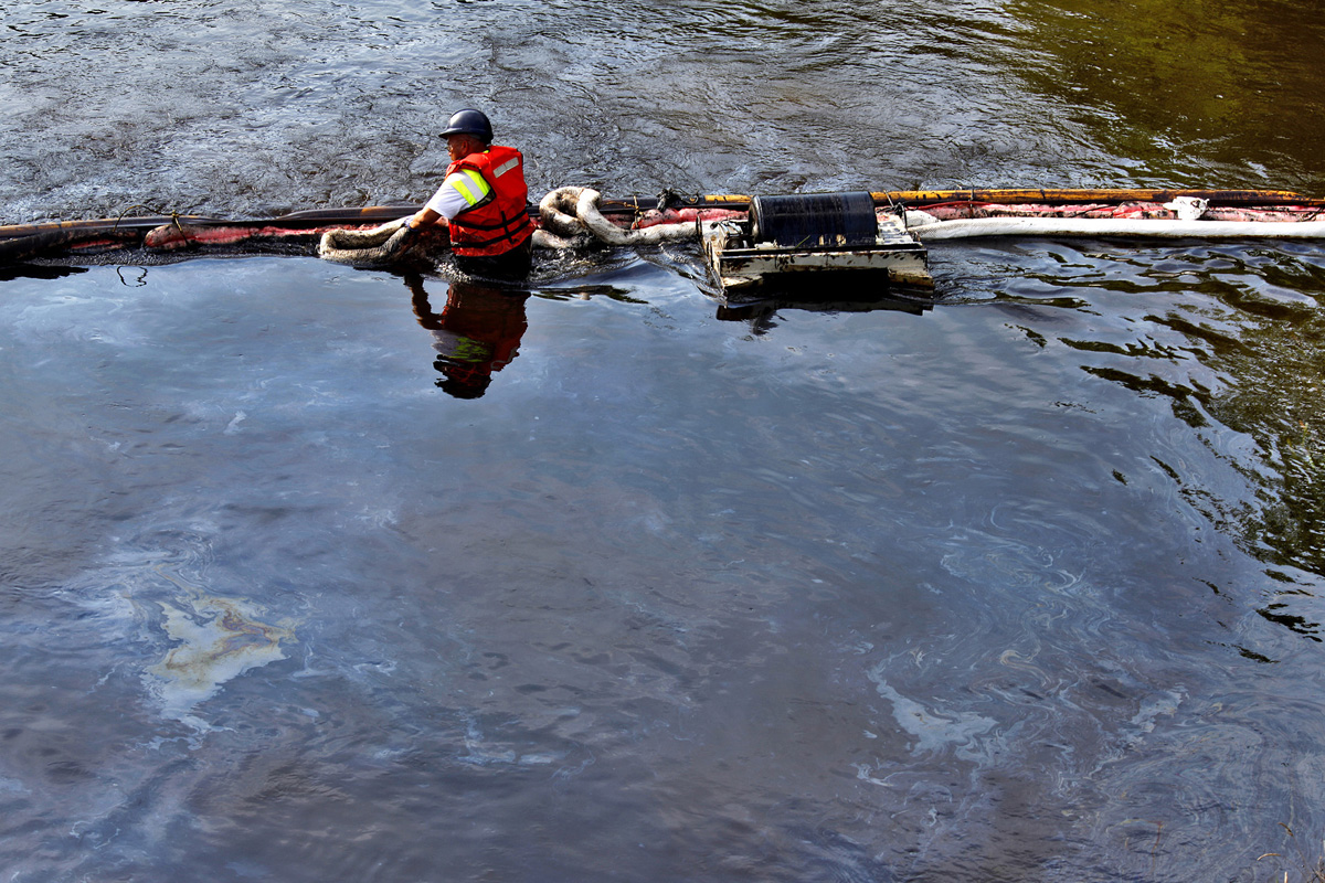 Cleanup crews adjust an oil containment boom in the Kalamazoo River in Emmett Charter Township above S Wattles Road. More than 2,500 workers were needed to assist in the cleanup process.