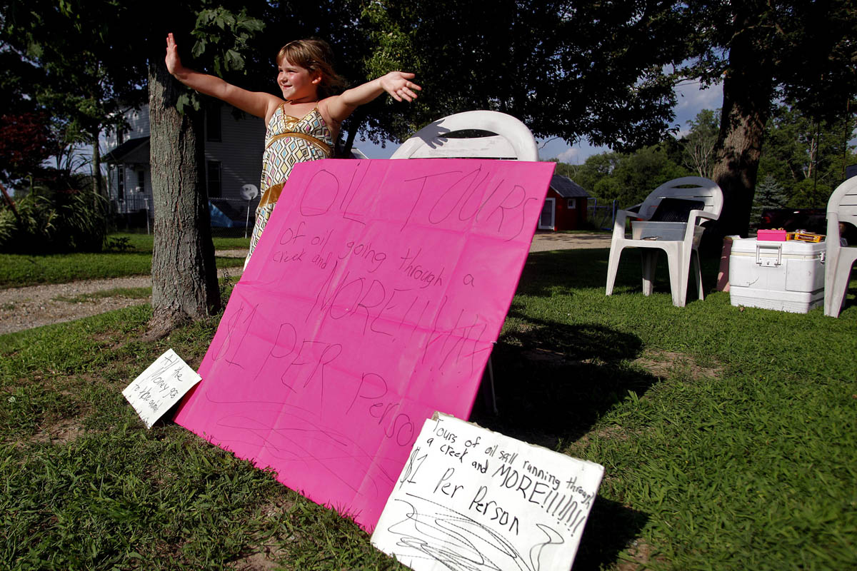 Mikayla Dogan, 6, of Marshall tries to get attention of passing motorists along 15 Mile Road to pay for an {quote}oil tour{quote} in Marshall. The tour consisted of walking through the Dogan's backyard to Talmadge Creek where the oil spill began. The cost of the tour was a dollar per person with all proceeds being donated to helping the wildlife.