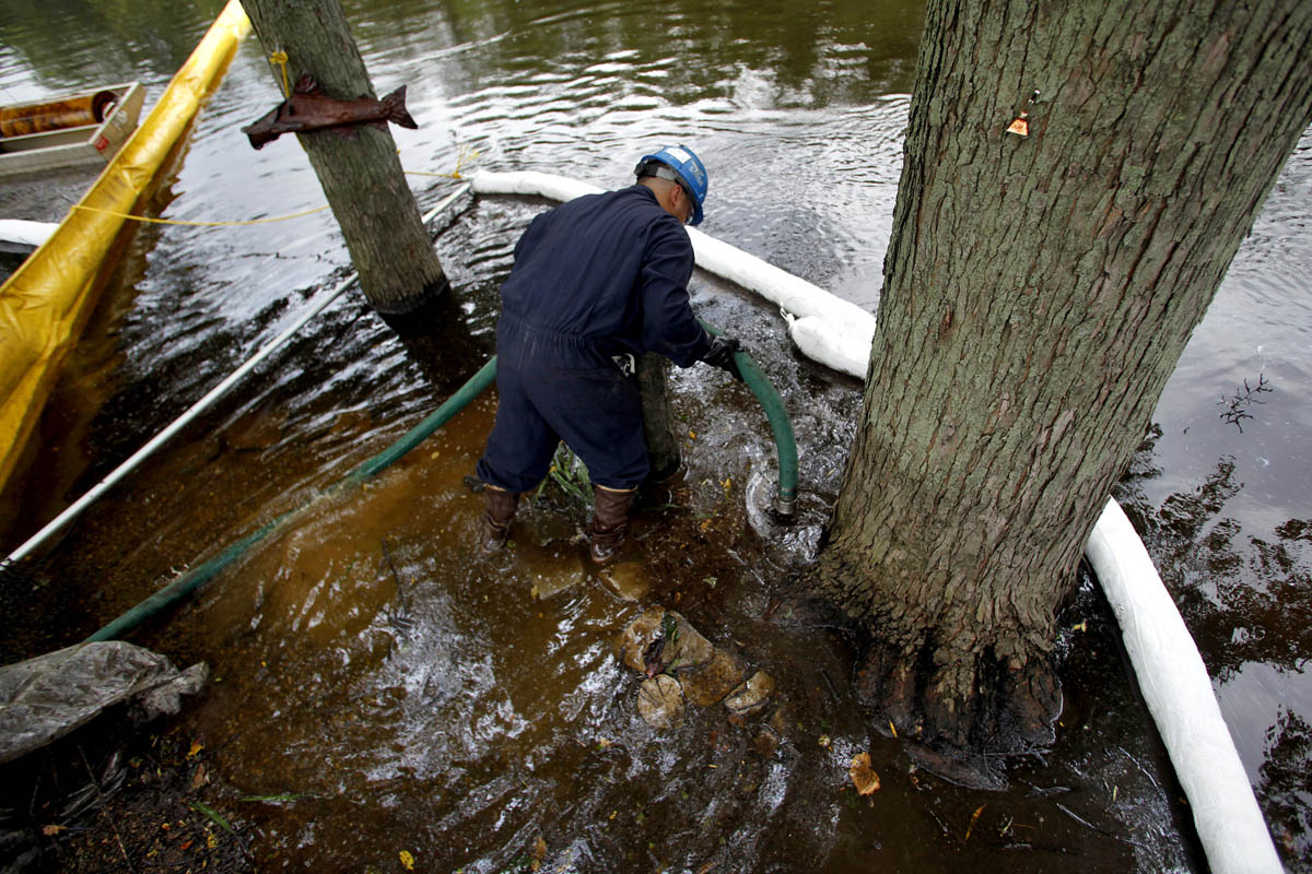 Raul Vervuzco of Eagle Services uses a suction hose to clean oil from atop the Kalamazoo River in a containment area in Augusta nearly 30 miles away from the original ruptured pipeline.