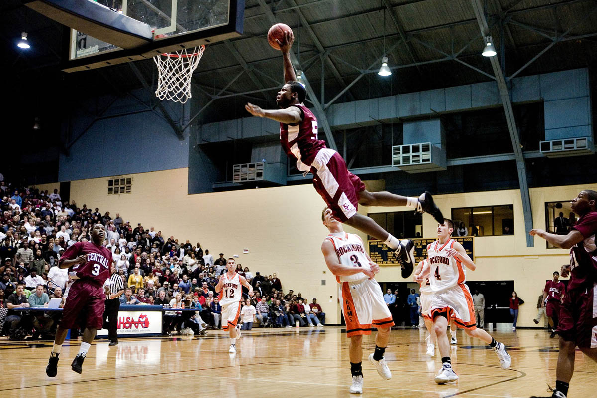 Kalamazoo Central's Doug Anderson, center, leaps over Rockford's Brogan Bibler, 3, as he attempts to dunk the ball during the 2009 Class A state quarterfinal basketball game at Lansing Eastern High School's Don Johnson Fieldhouse.