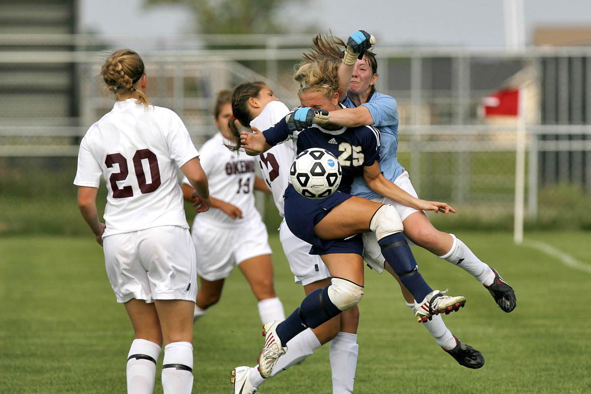 Portage Central's Paige Wester collides with Okemos goalie Baleigh Johnson while attacking the net during the 2010 Division 1 regional championship game at Holt High School. Portage Central won 4-2.