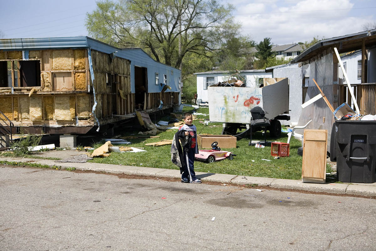 A young boy walks among discarded toys and trash as residents of Franklin Valley Estates mobile home park fill trailers and cars with only their most important possessions. At night over the past month, metal scavengers have come and helped themselves to aluminum siding from abandoned trailers and even from some occupied ones, several park residents said.