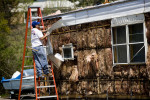 Pedro Morales helps remove the aluminum siding from Sylvia Ortega's, not pictured, mobile home to sell as scrap metal to assist with funds needed to vacate the Franklin Valley Estates mobile home park. {quote}I was the first one in the park to take the siding off my place. It's mine, so I might as well get something out of it,{quote} said Ortega.