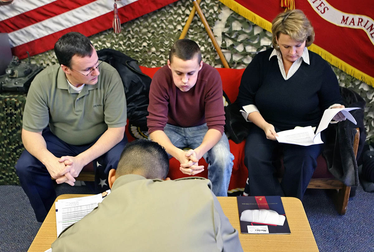 David Wrench, center, takes a deep breath at the Portage Recruitment Center as Staff Sgt. Shoji Harris goes over final paperwork and preparations for David's departure into U.S. Marine Corps boot camp in San Diego. David is flanked by his father, Tom Wrench, and mother, Jonna Jameson. The 18-year-old graduated early from Plainwell High School in order to leave for boot camp.