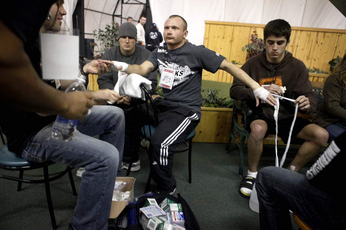 Mike Wood, center, sits nervously as his hands are taped by fighters he trains with at Lightning Kicks in Kalamazoo. Wood was competing in his first mixed martial arts match during Rumble in the Zoo at Year Round Golf in Schoolcraft.