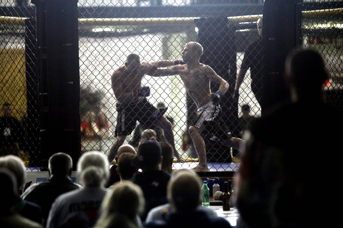Mixed martial arts fans watch intently as Mike Wood, left, and Mike Thackston begin their mixed martial arts match.