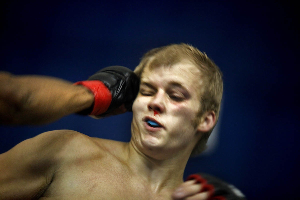 Eric Zapata, left, delivers a punishing blow to Zach Strang's head during their mixed martial arts match. Zapata continued to deliver punches and shortly after knocked Strang out.