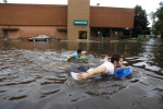 Western Michigan University students Ryan Ehmann, 20, left, and Rusty Good, 19, swim through the National City Bank parking lot on bodyboards after heavy rainstorms caused flooding in parts of Kalamazoo leaving many roads impassable.