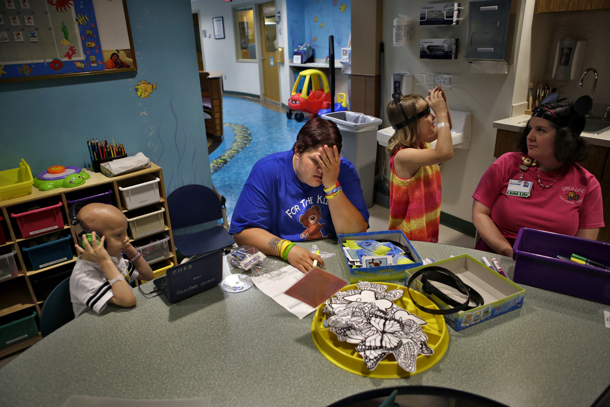Michelle Bulich, center, holds her head in disappointment after receiving her five-year-old son, E.J.'s, left, lab results at Children's Hospital of The King's Daughters Thursday afternoon. The lab results stated that E.J. would a second blood transfusion in less than one week and increase the families time in the hospital. To the right is Michelle's daughter, Emma, 6, talking with child life assistant Nicky Wells. E.J. is diagnosed with stage three neuroblastoma and Emma is in remission for leukemia.