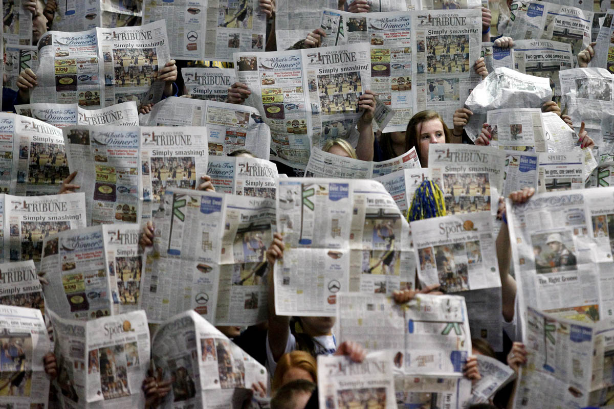 Grand Haven fans hold up newspapers to show their lack of interest as an announcer reads the starting lineup of Kalamazoo Central's basketball team during the 2010 Class A playoff game at Lansing Eastern's Don Johnson Fieldhouse.